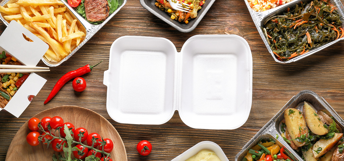 Different types of food containers including styrofoam, paper, and aluminum with food in them on top of a wooden table