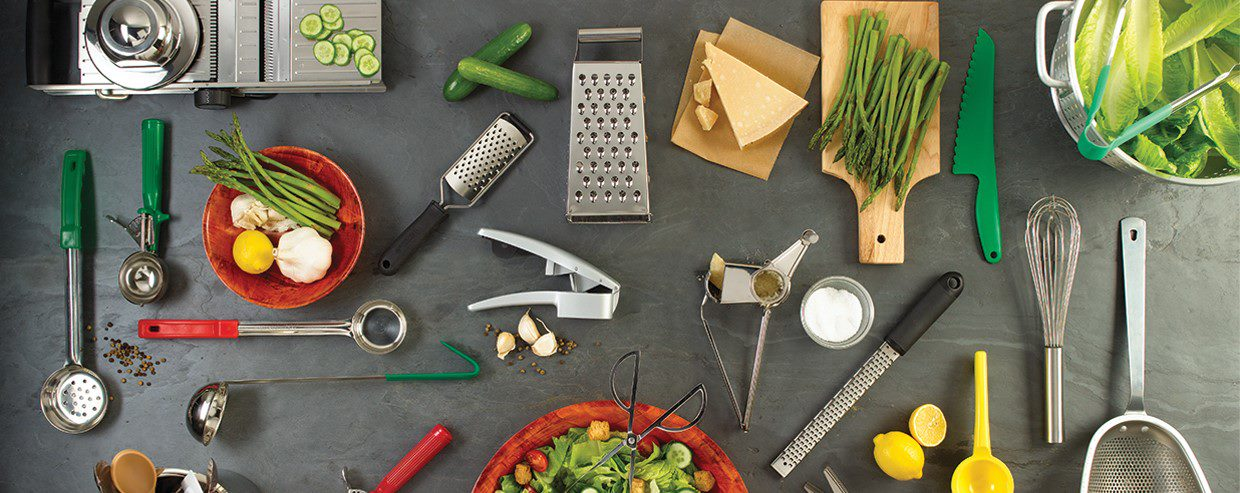 Countertop full of different types of small kitchen utensils including a whisk, bowls, measuring utensils, cheese graters, and a garlic press